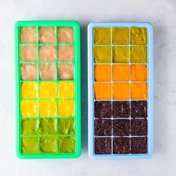 2 silicone ice cube trays with homemade colorful baby food.