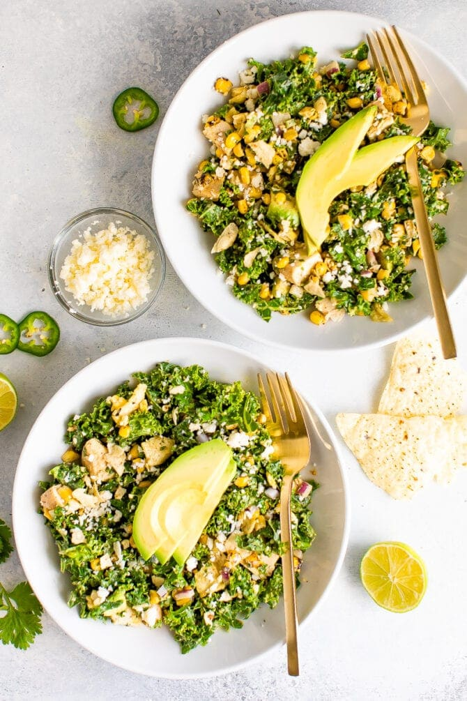 Two white bowls filled with kale Mexican street corn salad with grilled chicken and topped with slices of avocado. Two gold forks are resting on the side of the plates. On the table, cilantro, a bowl of cheese, slices of jalapeno and lime and tortilla chips are scattered.