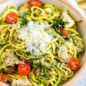 Ceramic bowl with pesto zucchini noodles with chicken and cherry tomatoes, topped with parmesan.