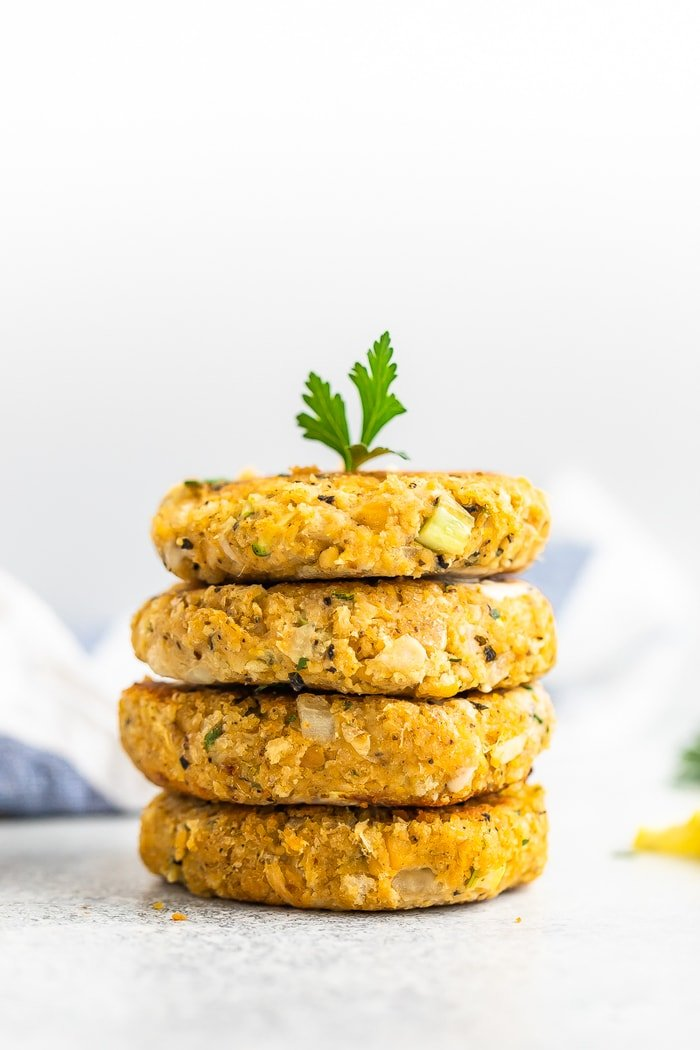 Stack of 4 vegan crab cakes topped with a sprig of fresh parsley.