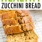 Loaf of zucchini bread with 4 thick slices cut on a gold wire cooling rack.