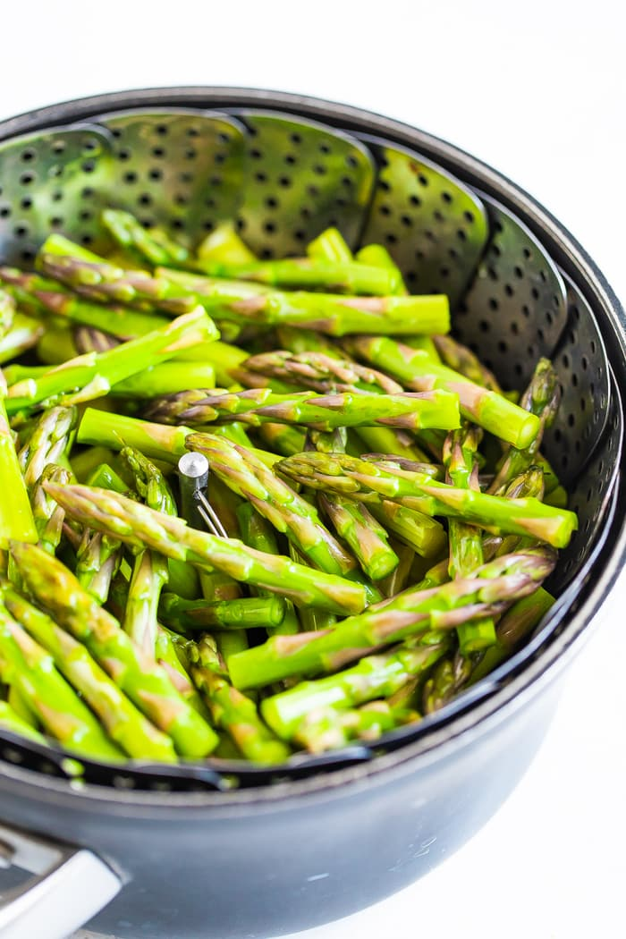 Asparagus spears in a steamer basket in a pot.