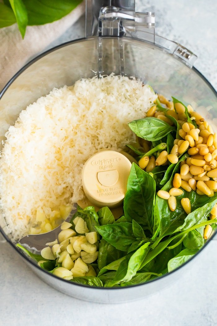 Food processor with parmesan, pine nuts, fresh basil, garlic and olive oil.
