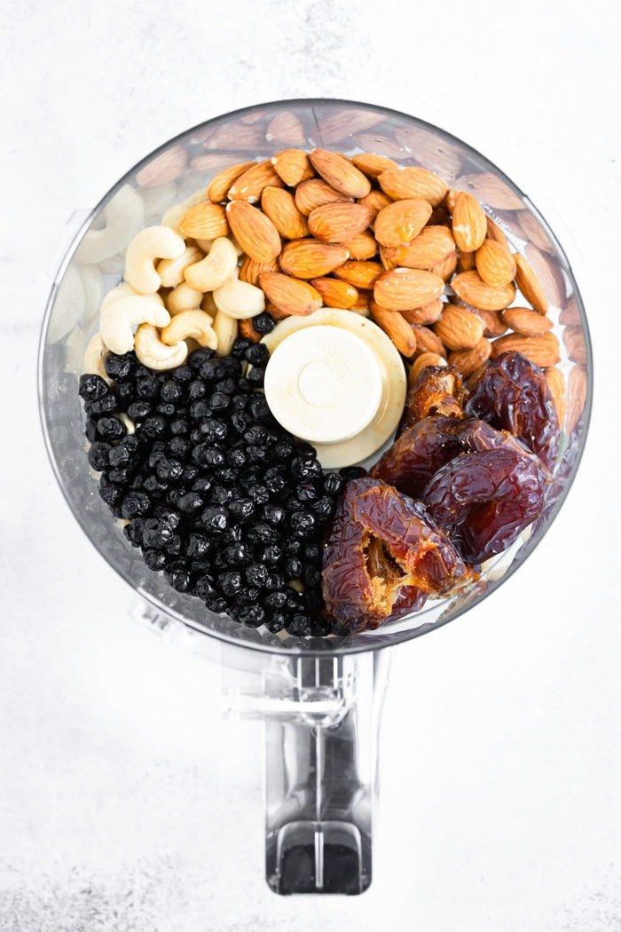 Food processor with dried blueberries, dates, almonds and cashews.