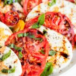 Close up photo of a caprese salad, slices of tomato and fresh mozzarella topped with balsamic, pepper and basil.