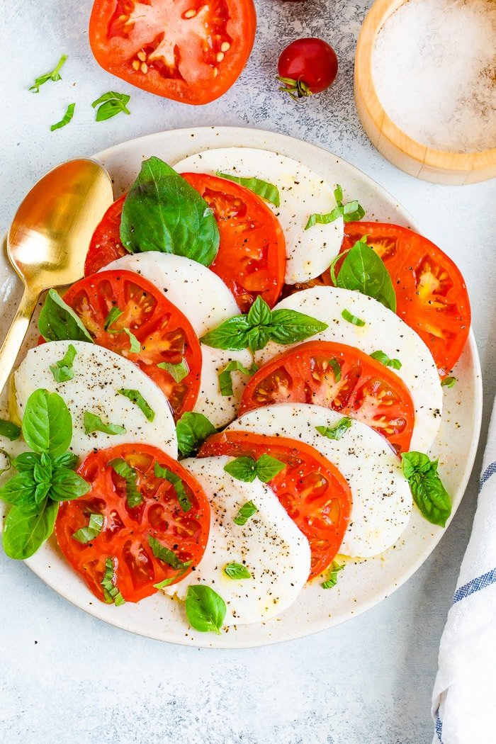 Thick slices of tomato and fresh mozzarella on a plate with a gold spoon and topped with pepper and fresh basil.