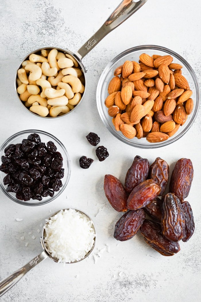 Cashews, almonds, dried cherries, coconut and dates measured out on a table.