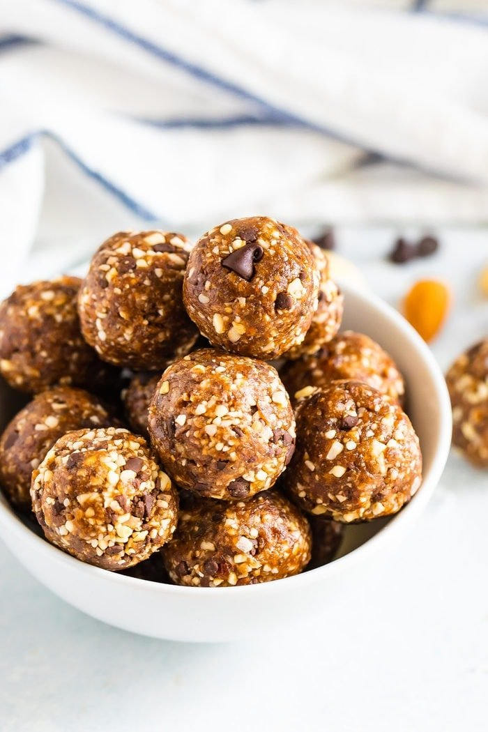 White bowl full of coconut chocolate chip energy balls.