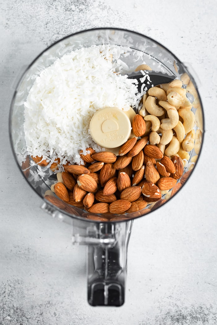 Food processor with coconut flakes, cashews and almonds.