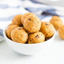 White bowl full of cookie dough protein balls.