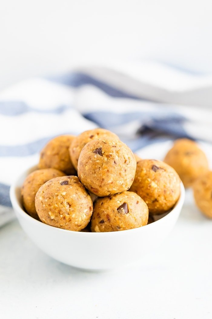 White bowl full of chocolate chip cookie dough protein balls.