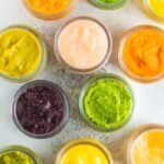Overhead photo of glass baby food jars filled with 6 different types of homemade baby food.