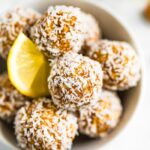 Bowl full of lemon energy balls rolled in coconut flakes. Slice of lemon is in the bowl.