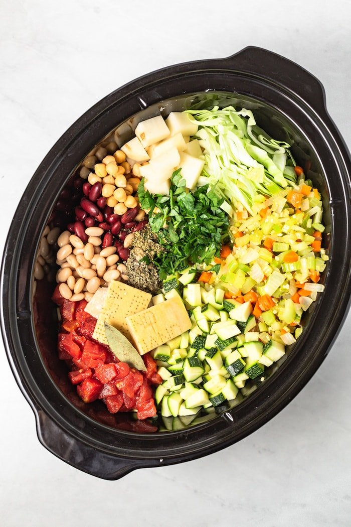 Slow cooker filled with ingredients for minestrone soup.