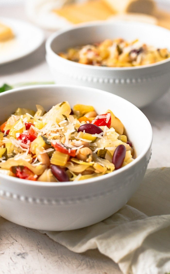 A white bowl with minestrone soup with shredded parmesan on top.