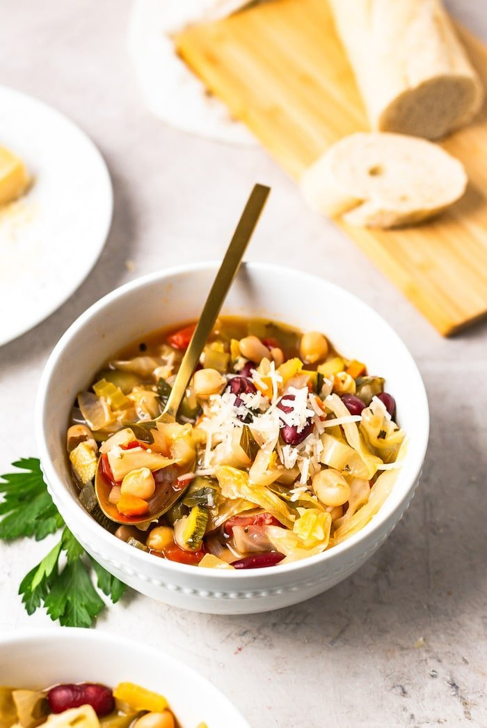A white bowl with minestrone soup with shredded parmesan on top and a gold spoon.