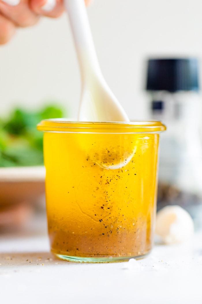 White spoon stirring a jar white balsamic vinaigrette.