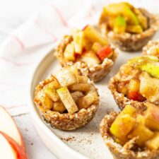 Mini raw apple pies on a plate. A napkin and apple slices are also on the table.