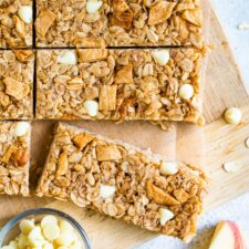 Apple granola bars on a wood board next to a bowl of white chocolate chips and apple slices.
