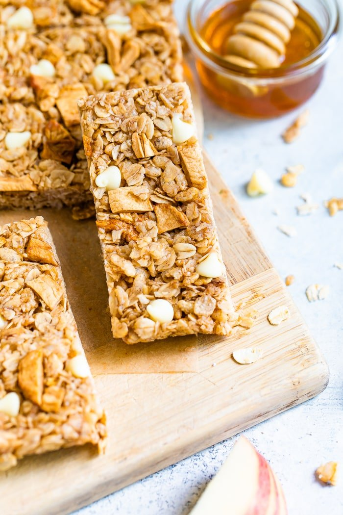 Apple granola bar on a wood cutting board next to a bowl of honey.