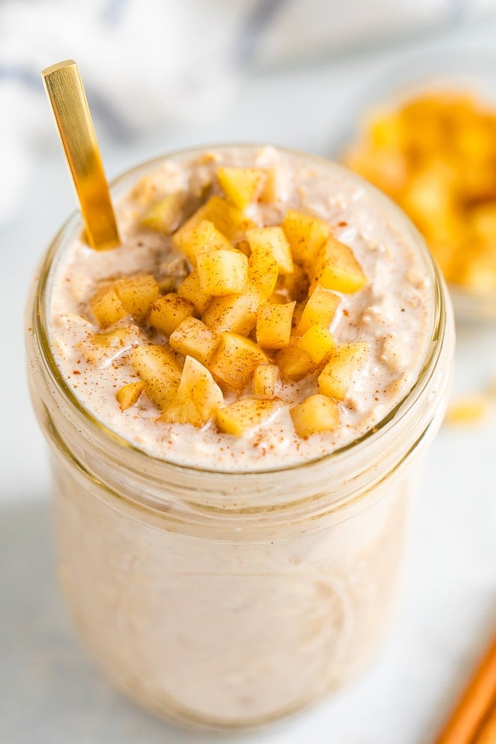 Glass jar with apple pie overnight oats topped with cinnamon apple chunks. A gold spoon is in the jar.