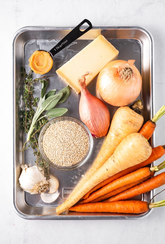 Tray with ingredients for carrot parsnip soup like onions, herbs, cheese, garlic and carrots and parsnips.