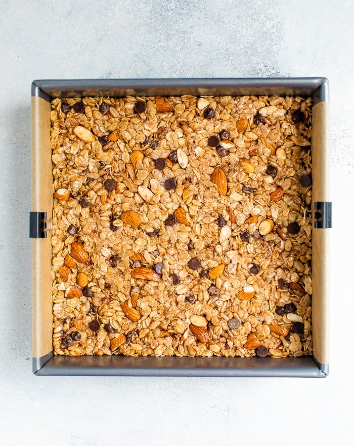 Square pan with chocolate chip almond granola bars before being cut.