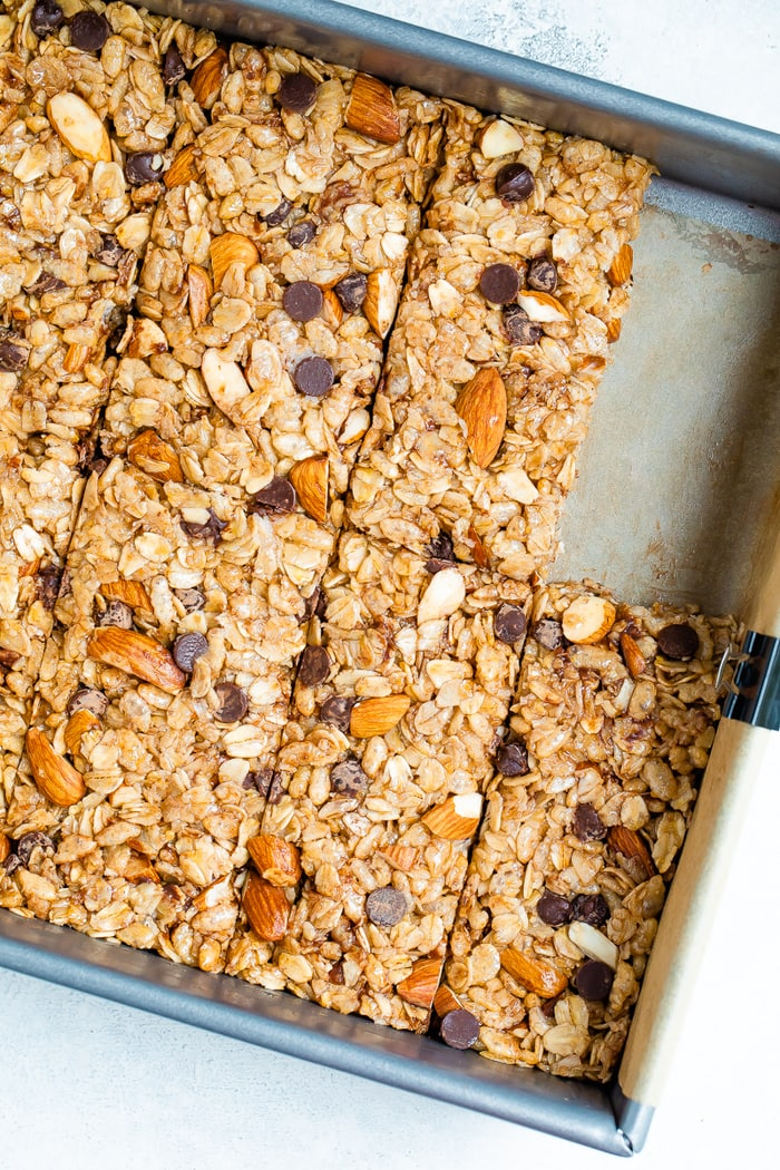 Metal pan with chocolate chip almond granola bars cut into bars.