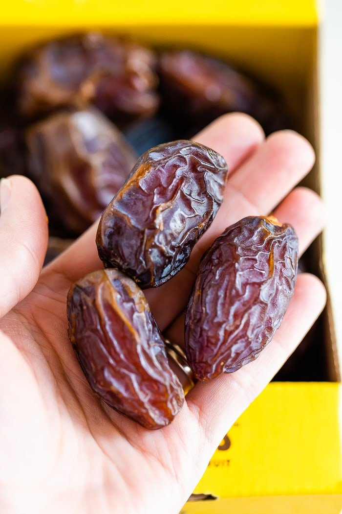 Three medjool dates in a woman's hand.