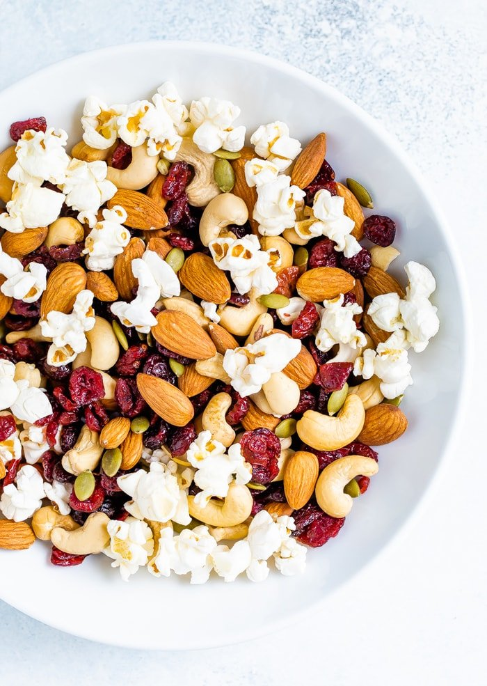 Bowl of trail mix made with popcorn, nuts and cranberries.