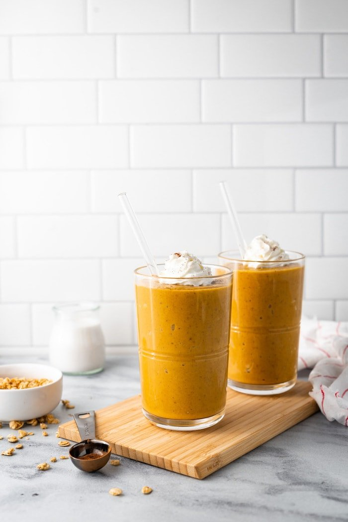 Two pumpkin pie smoothies on a wood cutting board surrounded by spices and a kitchen towlel.