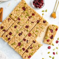 Pumpkin spice granola bars neatly on a table surrounded by pepitas, cranberries and cinnamon.