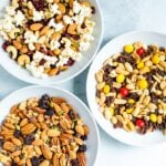Three bowls of different trail mixes.