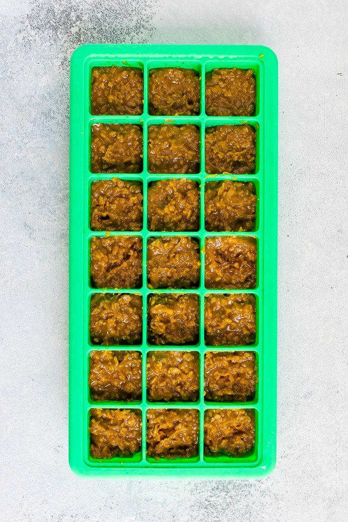 Butterfinger bites in a green silicone ice cube tray.