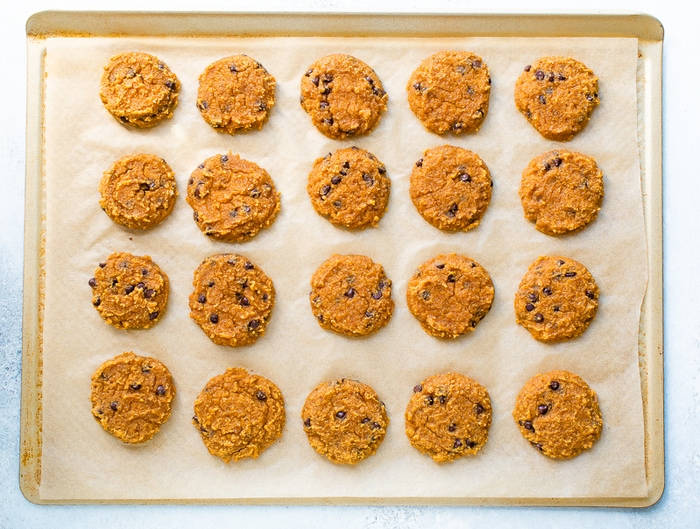 20 cooked pumpkin cookies on a gold baking sheet lined with parchment.