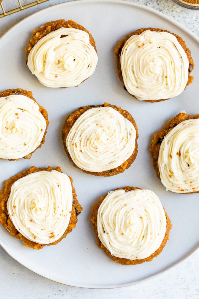 Plate with iced pumpkin cookies.
