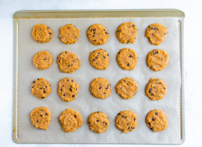 20 unbaked pumpkin cookies on a gold baking sheet lined with parchment.