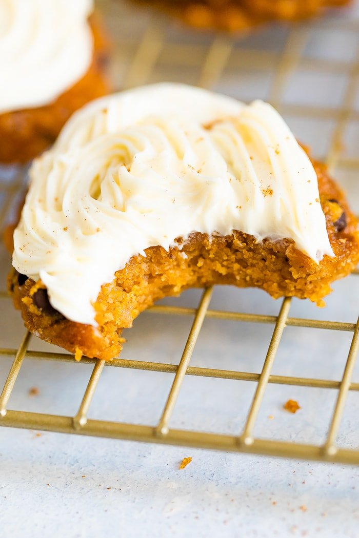 Pumpkin cookie topped with icing and a bite is taken out of it.