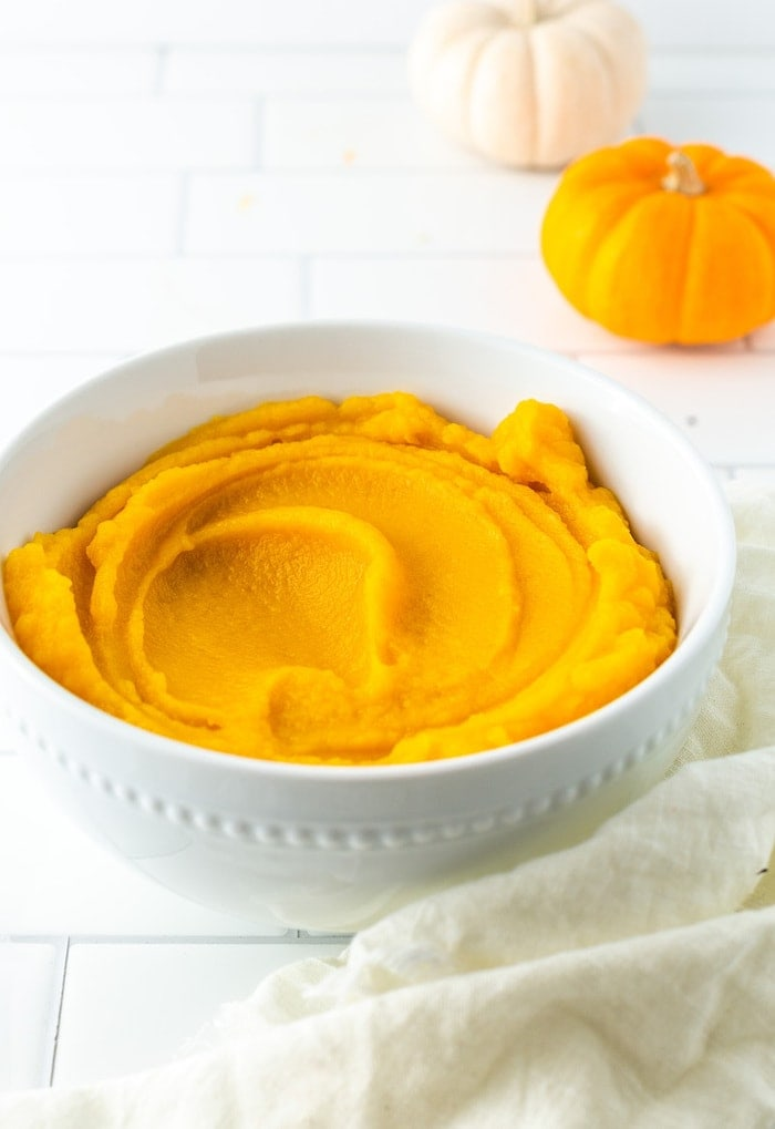 Bowl with pumpkin puree. A cloth and mini pumpkins are on the table around the bowl.