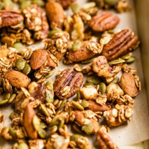 Spiced seeds, nuts and oats on a baking sheet.