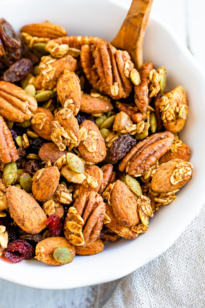 Bowl with a small wooden spoon full of pumpkin spice nutty and fruity trail mix.