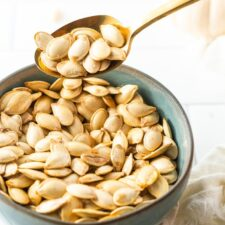 Spoon scooping up some roasted pumpkin seeds from a bowl.