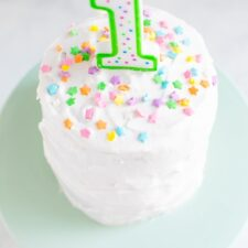 """Small smash cake with white frosting, a """"1"""" birthday candle and colorful star sprinkles."""