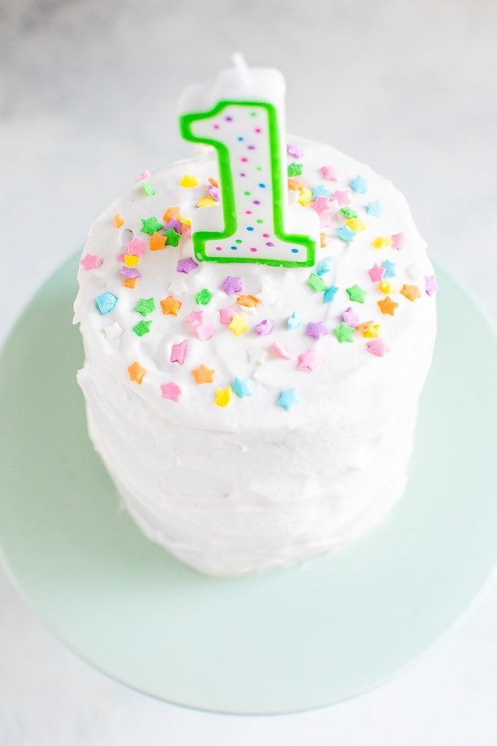 "Small smash cake with white frosting, a ""1"" birthday candle and colorful star sprinkles."