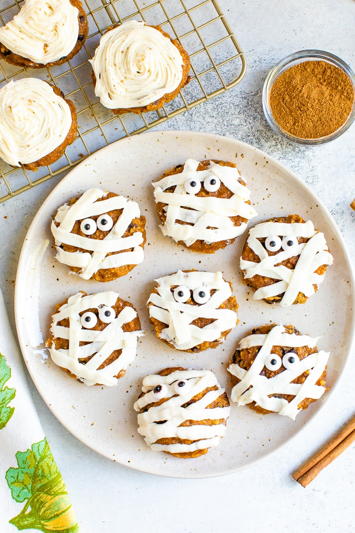 Plate with cute mummy cookies. Pumpkin cookies frosted with stripes of white icing and two candy eyes.
