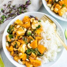 Bowls of tofu pumpkin curry topped with cashews and served with rice.