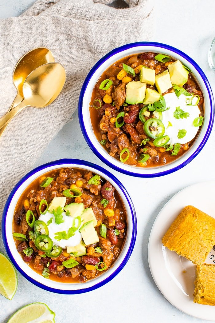 Bowls of turkey chili served with avocado, sou cream and cornbread.