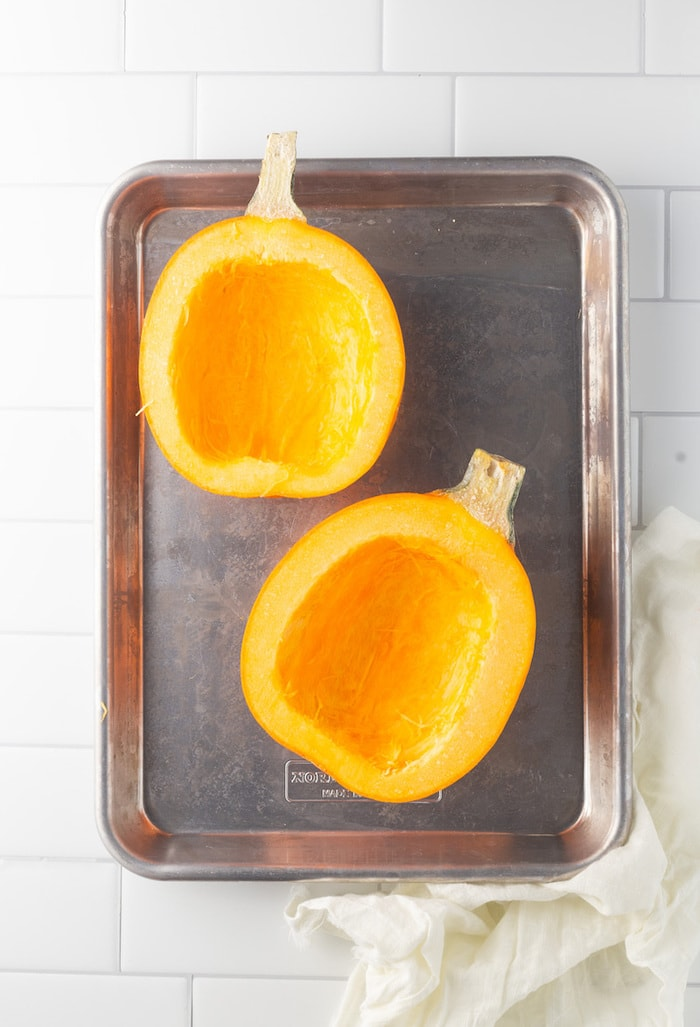 Sheet pan with two halves of pumpkin.