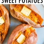 Three baked sweet potatoes on a plate topped with butter, salt and pepper.