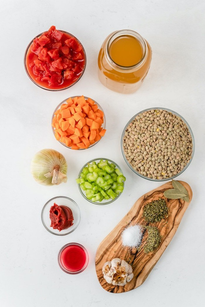 Ingredients to make lentil soup including tomatoes, broth, carrots, lentils, onion, celery, tomato paste, garlic, vinegar and spices.